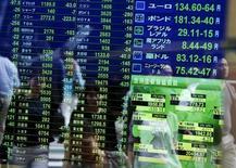 Peatones reflejados en un tablero electrónico que muestra la información de las acciones, en una correduría en Tokio, Japón, 29 de septiembre de 2015. Las bolsas de Asia exhibían desempeños dispares el miércoles en momentos en que los inversores se mantenían cautelosos antes de la reunión de política monetaria del Banco Central Europeo más tarde en la semana, aunque el mercado japonés saltó a un nuevo máximo en un mes. REUTERS/Issei Kato