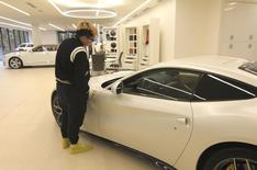 A young customer checks out a Ferrari at a luxury car dealership in Vancouver, British Columbia, in this picture taken October 10, 2015. REUTERS/Julie Gordon