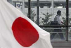 Бизнесмен проходит мимо флага Японии в Токио. 24 августа 2011 года. Суверенный рейтинг Японии вряд ли будет меняться в ближайшие годы благодаря низкой стоимости финансирования госдолга, сказал представитель международного рейтингового агентства Moody's Investors Service Кристиан де Гусман в четверг. REUTERS/Issei Kato