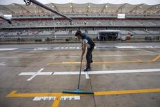 A Williams Formula One pit crew member clears rain water from pit lane ahead of the first practice session of the U.S. F1 Grand Prix at the Circuit of The Americas in Austin, Texas October 23, 2015.    REUTERS/Adrees Latif