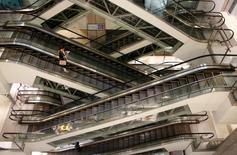 A woman rides an escalator at a shopping mall in Beijing, China, September 23, 2015. REUTERS/Kim Kyung-Hoon