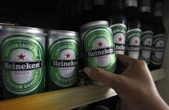 Una mujer toma una lata de cerveza Heineken en un restaurante en Bangkok, 20 de julio de 2012.  Heineken NV, la tercera mayor cervecera del mundo, dijo el miércoles que sus ingresos y volúmenes de cerveza aumentaron más de lo previsto en el tercer trimestre, impulsados por fuertes ventas en Latinoamérica y un verano más cálido en buena parte de Europa. REUTERS/Sukree Sukplang