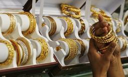 Женщина примеряет золотой браслет в ювелирном магазине в индийском городе Ноида. 21 апреля 2011. Продажи товаров класса люкс в мире снизились в 2015 году на фоне слабого спроса в Китае и Гонконге, замедлив темп роста в годовом исчислении при неизменных валютных курсахдо 1-2 процента с 3 процентов годом ранее, говорится в исследовании консультационной компании Bain & Co. REUTERS/Parivartan Sharma
