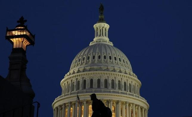 A man walks past the United States Capitol Dome before dawn in Washington March 22, 2013. REUTERS/Gary Cameron (UNITED STATES - Tags: POLITICS CITYSCAPE) - RTR3FBOX