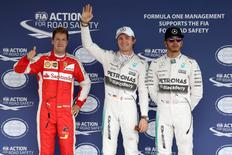 Mercedes' Nico Rosberg (C) celebrates qualifying in pole position with second placed Mercedes' Lewis Hamilton (R) and Ferrari's Sebastian Vettel who qualified in third place. Mandatory Credit: Action Images / Hoch Zwei