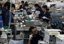 Employees work an assembly line at a factory of Glory Ltd., a manufacturer of automatic change dispensers, in Kazo, north of Tokyo, Japan, July 1, 2015. REUTERS/Issei Kato