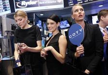 Unas modelos reunidas en el puesto donde se transan acciones de Coty en la bolsa de Nueva York, hun 13, 2013. El fabricante de perfumes Coty Inc comprará el negocio de cuidado personal y belleza de la brasileña Hypermarcas SA por unos 1.000 millones de dólares en efectivo, tres meses después de acordar la compra de 43 marcas similares de Procter & Gamble.  REUTERS/Brendan McDermid