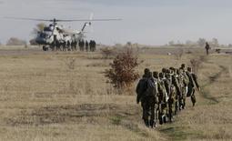 """Российские парашютисты идут к вертолету во время учений близ Ставрополя 27 октября 2015 года. Девять стран-членов НАТО в Центральной, Восточной Европе и Балтии выразили """"серьезную озабоченность агрессивной позицией"""" России и высказались за постоянное присутствие военных альянса на его восточных границах. REUTERS/Eduard Korniyenko"""