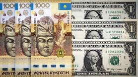 Банкноты тенге и доллара США. Алма-Ата, 21 августа 2015 года. Средневзвешенный курс тенге, упавший за неделю более чем на шесть процентов после смены главы Нацбанка, показывает новые минимумы, ЦБ, по мнению участников рынка, не вмешивается в процесс. REUTERS/Shamil Zhumatov
