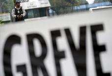 """Un guardia de seguridad detrás de una pancarta que dice """"huelga"""", frente a la Refinería de Duque de Caxias, cerca de Río de Janeiro, Brasil, 3 de noviembre de 2015. Líderes sindicales brasileños dijeron el jueves que un respaldo mayor que el esperado a una huelga en Petrobras se debe a la creciente oposición de los trabajadores a una progresiva privatización de la empresa petrolera estatal. REUTERS/Ricardo Moraes"""