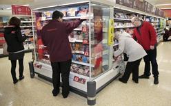 Покупатели и сотрудники в магазине Sainsbury's в Лондоне 23 октября 2015 года. Прибыль британской сети супермаркетов Sainsbury's за первое полугодие уменьшилась на 18 процентов в связи с продуктовой дефляцией, в том числе со снижением цен на товары в ее магазинах. REUTERS/Suzanne Plunkett