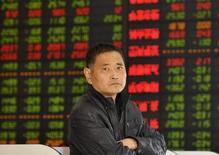 Un inversor frente a un tablero electrónico que muestra información bursátil, en una correduría en Fuyang, China, 2 de noviembre de 2015. Las acciones chinas cerraron el viernes luego de que los valores ligados a la manufactura y la energía lastraron a los principales índices del país. REUTERS/Stringer