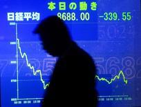 Японский бизнесмен идет мимо табло с котировками фондового рынка в Токио.  Экономика Японии снова впала в рецессию в третьем квартале на фоне неопределенности на внешних рынках, которая привела к спаду инвестиций в бизнес.  REUTERS/Yuriko Nakao  YN/JS