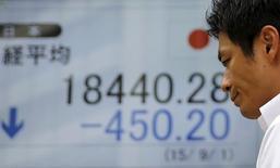 Un hombre camina delante de un tablero electrónico que muestra el índice Nikkei de Japón, afuera de una correduría en Tokio, 1 de septiembre de 2015. El índice Nikkei de la bolsa de Tokio cayó el lunes a un mínimo en más de una semana luego de que las acciones de los exportadores, las líneas aéreas y las agencias de viajes fueron golpeadas por un declive del apetito por el riesgo por los ataques mortales de milicianos islamistas en París. REUTERS/Toru Hanai