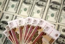 Рублевые и долларовые купюры. Сараево, 9 марта 2015 года. Рубль удерживает плюс на биржевых торгах понедельника, достигнутый за счет продаж экспортной валютной выручки и привлекательности рублевых активов с точки зрения доходности на фоне нынешнего дифференциала ставок ФРС и ЦБР, но при этом утратив поддержку от неудачных внутридневных попыток восстановления нефти. REUTERS/Dado Ruvic