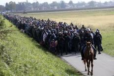 Полиция сопровождает группу беженцев в Словении 20 октября 2015 года. Агентство ООН по делам беженцев во вторник призвалоевропейские страны не отказываться от приема мигрантов и воздержаться от обвинений в их адрес после серии атак, произошедших в пятницу вечером в Париже. REUTERS/Srdjan Zivulovic