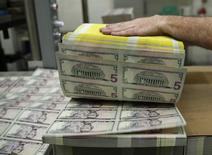 Billetes de cinco dólares durante su elaboración en la Casa de la Moneda de Estados Unidos en Washinghton, mar 26, 2015. El dólar se apreciaba el martes después de que una leve alza de un índice de inflación en Estados Unidos reforzó las expectativas de que la Reserva Federal subirá las tasas de interés en diciembre.  REUTERS/Gary Cameron