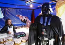 Дарт Вейдер, лидер Интернет-партии Украины, держит кусок мяса на рынке в Киеве. 3 апреля 2014 года. Российское правительство приняло решение о введении в отношении украинских товаров продовольственного эмбарго с начала следующего года, тогда же перестанет действовать режим свободной торговли между Украиной и Россией. REUTERS/Shamil Zhumatov
