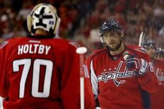 Oct 10, 2015; Washington, DC, USA; Washington Capitals left wing Alex Ovechkin (8) celebrates with Capitals goalie Braden Holtby (70) after scoring a goal against the New Jersey Devils in the third period at Verizon Center. The Capitals won 5-3. Mandatory Credit: Geoff Burke-USA TODAY Sports