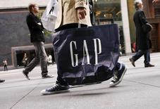 Человек с пакетом Gap на 5-й авеню в Нью-Йорке 8 октября 2009 года. Продавец одежды Gap Inc снизил прогноз прибыли на 2015 год из-за укрепления доллара и слабых продаж торговых марок Banana Republic и Gap, однако глава компании Артур Пек сказал, что весной могут произойти улучшения. REUTERS/Lucas Jackson