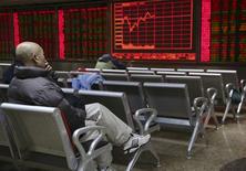 Un inversor frente a un tablero electrónico que muestra la información de las acciones, en una correduría en Pekín, 18 de noviembre de 2015. Las acciones chinas cerraron estables el viernes luego de que unas nuevas medidas del estímulo del banco central fueron contrarrestadas por la cautela antes de una serie de salidas a bolsa. REUTERS/Li Sanxian