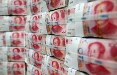 Пачки юаней в отделении банка в Сеуле. 8 октября 2010 года. Юань может быть включен в перечень резервных валют Международного валютного фонда, однако вес китайской валюты в корзине, вероятно, окажется ниже ожидаемых 14-16 процентов, сообщили Рейтер источники, знакомые с ходом обсуждения вопроса. REUTERS/Lee Jae-Won
