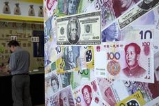 Un cliente es atendido en una casa de cambio en Hong Kong, China, 13 de agosto de 2015. Las autoridades chinas descubrieron el mayor caso de banca informal en el país, que involucra transacciones por un total de más de 410.000 millones de yuanes (64.000 millones de dólares), informó la prensa oficial, en medio de una campaña para combatir la salida ilegal de capitales. REUTERS/Tyrone Siu