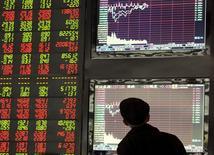 Инвестор в брокерской конторе в Фуяне. 30 октября 2015 года. Китайские акции снизились в понедельник в связи с потерями в секторе телекоммуникаций и настороженностью инвесторов перед новой волной регистраций на бирже. REUTERS/Stringer