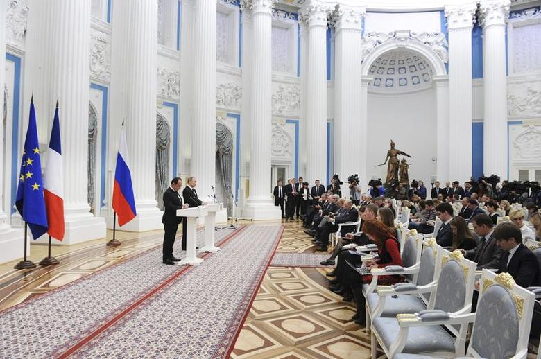 Russia's President Vladimir Putin (2nd L) and his French counterpart Francois Hollande (L) attend a news conference after a meeting at the Kremlin in Moscow, Russia, November 26, 2015. France and Russia agreed on Thursday to exchange intelligence on Islamic State and other militant groups in Syria to help improve the effectiveness of their aerial bombing campaigns in the country, French President Francois Hollande said. REUTERS/Mikhail Klimentyev/Sputnik/Kremlin ATTENTION EDITORS - THIS IMAGE HAS BEEN SUPPLIED BY A THIRD PARTY. IT IS DISTRIBUTED, EXACTLY AS RECEIVED BY REUTERS, AS A SERVICE TO CLIENTS.