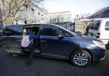 A primary school student gets into a minivan as her mother picks her up outside her school, in Beijing, November 25, 2015. REUTERS/Jason Lee