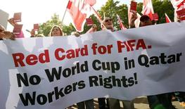 Members of the Swiss UNIA workers union display red cards and shout slogans during a protest in front of the headquarters of soccer's international governing body FIFA in Zurich October 3, 2013. REUTERS/Arnd Wiegmann