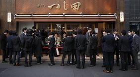 Executivos aguardando em fila de restaurante em Tóquio.  19/12/2014   REUTERS/Issei Kato