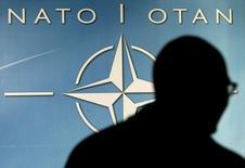 Мужчина проходит мимо логотипа НАТО в Брюсселе 1 декабря 2003 года. Министры иностранных дел НАТО в среду пригласили в альянс Черногорию, через 16 лет после западных бомбежек, которым бывшая югославская республика подверглась в ходе войны из-за Косово, и на фоне возражений из России. REUTERS/Thierry Roge