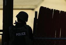 Офицер полиции, участвующий в поиске подозреваемых в стрельбе в Сан-Бернардино. 2 декабря 2015 года. Мужчина и женщина, подозреваемые в стрельбе в центре социальной помощи в Калифорнии в среду, в результате которой погибли 14 человек и 17 были ранены, убиты в перестрелке с полицией несколько часов спустя, сообщили власти. REUTERS/Mike Blake