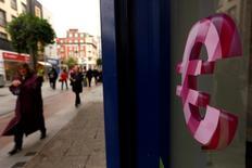 Символ евро в витрине магазина в Дублине. 22 октября 2014 года.  Курс евро достиг четырехнедельного максимума, а доходность облигаций выросла в четверг после того, как Европейский центробанк снизил депозитную ставку на 10 базисных пунктов до минус 0,30 процента годовых, не так сильно, как ожидал рынок. REUTERS/Cathal McNaughton