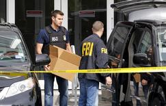 FBI agents remove boxes and other items from the offices of Imagina in Miami, Florida December 3, 2015.   REUTERS/Joe Skipper