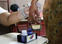 Una mujer entinta su dedo como prueba de que votó en las elecciones legislativas venezolanas, en Maracaibo, Venezuela, 6 de diciembre de 2015. Los precios de los bonos venezolanos en dólares subían hasta tres centavos de dólar el lunes, impulsados por la victoria de la oposición en las elecciones parlamentarias del fin de semana que generaron expectativas de reformas en el país petrolero. REUTERS/Isaac Urrutia