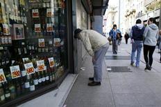 Una persona mira hacia una tienda, en el centro de Santiago, 26 de agosto de 2014. Los precios en Chile registraron una variación nula en noviembre, una lectura mejor a la esperada por el mercado que contribuyó a reducir también la inflación acumulada en lo que va del año, indicaron datos difundidos el lunes por el Gobierno. REUTERS/Ivan Alvarado