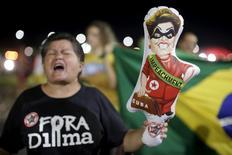 """Una mujer usa una franela donde se lee """"Fuera Dilma"""" y sostiene un globo durante una protesta contra la presidenta de Brasil, Dilma Rousseff, cerca de la sede del Gongreso en Brasilia, 2 de diciembre de 2015.  La agencia Moody's Investor Service colocó el miércoles la calificación soberana de Brasil en revisión para una posible baja a categoría especulativa, por un rápido deterioro del panorama macroeconómico y fiscal y el creciente riesgo de una parálisis política. REUTERS/Ueslei Marcelino"""