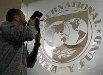 A photographer takes pictures through a glass carrying the International Monetary Fund (IMF) logo during a news conference in Bucharest March 25, 2009. The IMF has agreed a 20 billion euro aid package with Romania, including 12.9 billion euros of IMF money and 5 billion euros from the European Union, the fund said on Wednesday.  REUTERS/Bogdan Cristel (ROMANIA BUSINESS POLITICS) - RTXD6GE