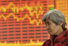 Un inversor frente a un tablero electrónico que muestra información bursátil, en una correduría en Fuyang, China, 4 de diciembre de 2015. Las acciones chinas cerraron el viernes en un mínimo en casi dos semanas, luego de que un desplome del yuan y los problemas del conglomerado Fosun Group debilitaron la confianza de los inversores. REUTERS/China