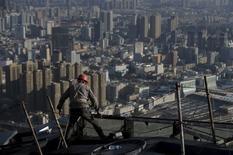 Рабочий на месте строительства жилого комплекса в Кунмине. 12 декабря 2015 года. Данные об экономической активности в Китае превзошли ожидания в ноябре, при этом рост промышленного производства достиг максимума пяти месяцев, указывая на то, что волна стимулирующих мер, предпринимаемых Пекином, возможно, несколько укрепила хрупкую экономику. REUTERS/Wong Campion
