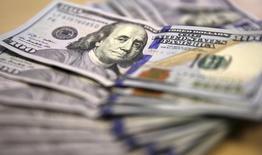 Банкноты доллара США. Йоханнесбург, 13 августа 2014 года. Доллар отодвинулся от отметки, близкой к недельному максимуму к корзине основных валют в среду, однако его потери были ограничены, в то время как рынок считает часы до вероятного повышения процентных ставок в США. REUTERS/Siphiwe Sibeko