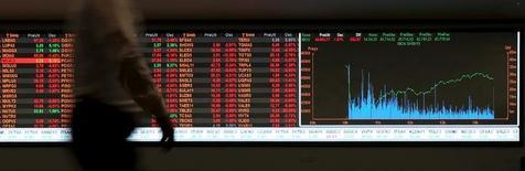 Мужчина проходит мимо экрана, отображающего котировки акций, на фондовой бирже BM&F Bovespa в Сан-Паулу. 24 августа 2015 года. Компании развивающихся рынков, имеющие задолженность в долларах и выручку в падающих местных валютах, могут столкнуться с трудностями, в то время как Федеральная резервная система США начинает, как ожидается, серию повышений процентных ставок спустя годы мягкой денежной политики. REUTERS/Paulo Whitaker