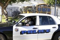 Полицейский говорит по рации рядом со школой в Лос-Анджелесе 15 декабря 2015 года. Власти Лос-Анджелесе сообщили, что в среду возобновят работу государственных школ, закрытых накануне из-за угрозы атак с использованием взрывчатки и огнестрельного оружия, которую позже сочли ложной. REUTERS/Jonathan Alcorn