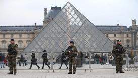 """French soldiers patrol in front of the Louvre Museum Pyramid's main entrance in Paris, France, as part of France's national security alert system """"Sentinelle"""" after Paris deadly attacks November 27, 2015.  REUTERS/Charles Platiau"""