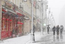 Люди во время снегопада в центре Москвы 22 марта 2015 года. Выходные в Москве будут теплыми и обещают осадки, свидетельствует усредненный прогноз, составленный на основании данных Гидрометцентра России, сайтов intellicast.com и gismeteo.ru. REUTERS/Sergei Karpukhin