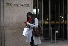 A visitor from China looks at her mobile phone after shopping at Tifany & Co. jewelers in New York City in this April 4, 2013 file photo.   REUTERS/Mike Segar/Files