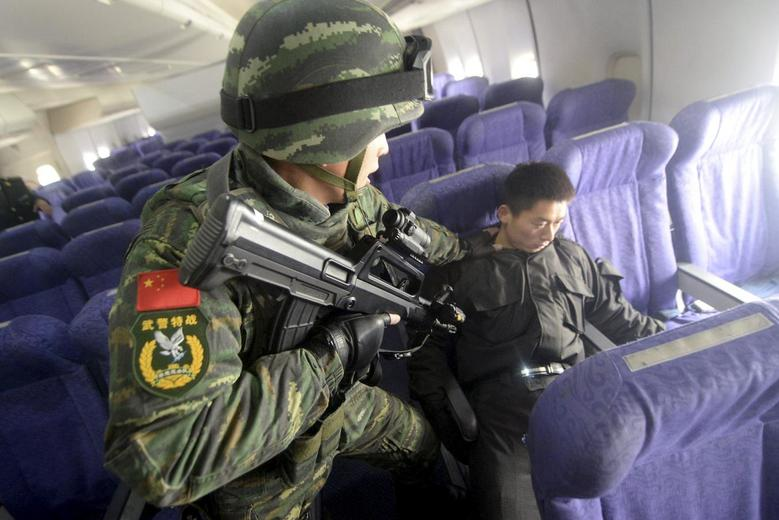 An armed paramilitary policeman checks a mock hijacker during an anti-terrorism drill on plane hijacking, on a passenger jet at the Beijing Capital International Airport, in Beijing, China, December 3, 2015. REUTERS/Stringer