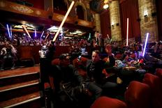 """Moviegoers cheers and wave lightsabers before the first showing of the movie """"Star Wars: The Force Awakens"""" at the TCL Chinese Theatre in Hollywood, California, December 17, 2015.    REUTERS/Mario Anzuoni"""